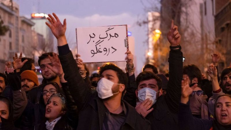 Manifestantes iranianos seguram cartaz que diz Morte ao Mentiroso