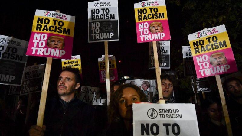Cartazes com a inscrição 'Não ao racismo, não a Trump'