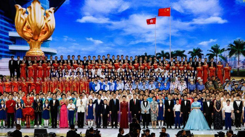 Çin Cumhurbaşkanı Xi Jinping (orta sağ, kırmızı kravat takma) bir şarkıyı söylüyor