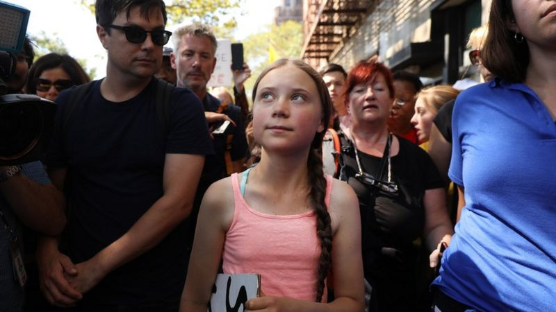 Greta walking through the streets of New york with people behind her