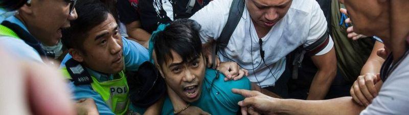 Pekin yanlısı bir destekçi, 1 Temmuz 2017'de Hong Kong'da bir Sosyal Demokratlar Birliği protestosunu durdurmaya çalışırken polis tarafından zorla kaldırıldı