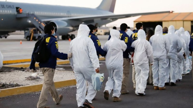 Police officers escorting deportees dressed in white medical suits to a Chilean Air Force plane