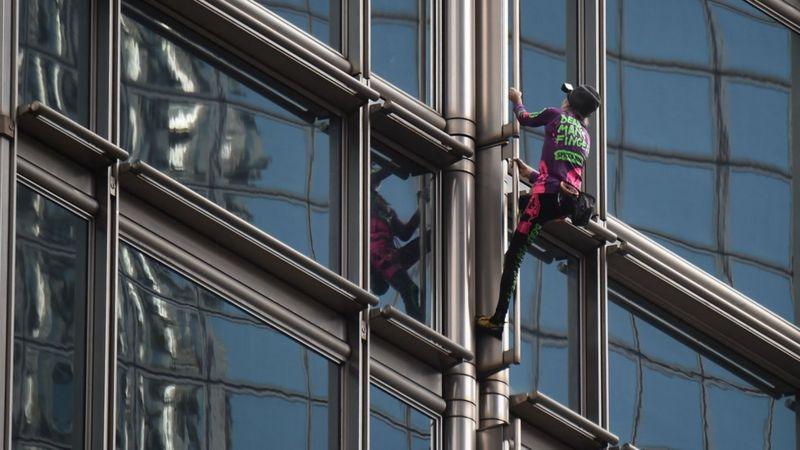 Seorang pendaki asal Perancis yang dikenal dengan sebutan 'Spiderman' memanjat gedung pencakar langit di Hong Kong dan memasang spanduk besar, Jumat (16/8/2019).