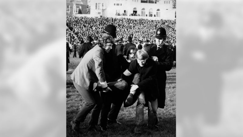 Protestor being carried off pitch