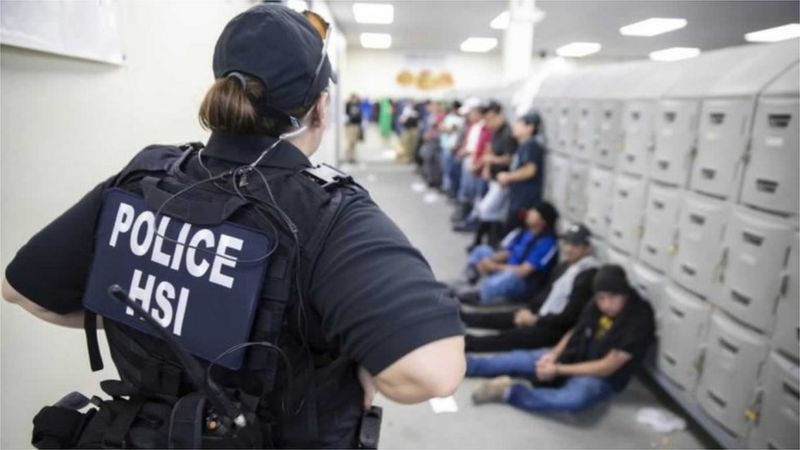 This image released by the US Immigration and Customs Enforcement (ICE) shows a Homeland Security Investigations (HSI) officer guarding suspected illegal aliens on August 7, 2019