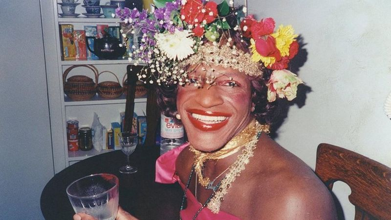 Gay Rights activist and visible transwoman Marsha P. Johnson smiling and wearing a crown made of flowers.