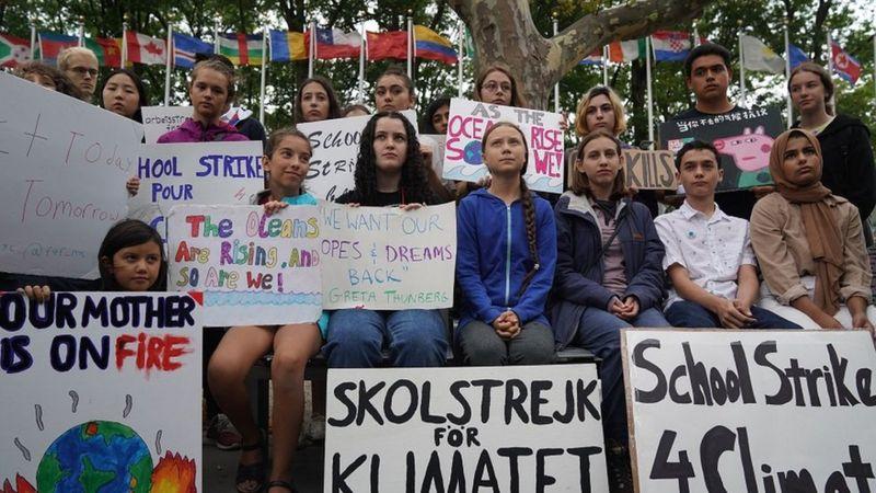 Greta sitting with school children on strike