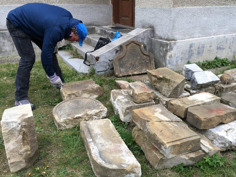 Tomas Jelinek cleaning some of the headstones