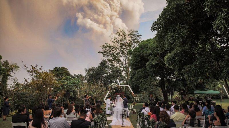 Foto de casamento com vulcão em erupção no fundo