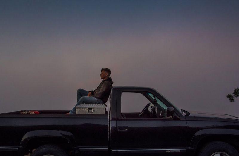 Retrato de Kase Dietrich sentado sobre seu carro