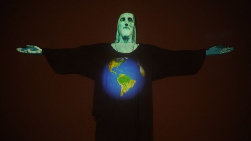 Estátua do Cristo Redentor à noite, iluminada por projeção mostrando um desenho do planeta em homenagem a vítimas da covid-19