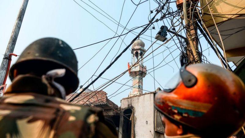 عناصر شرطية تقف في حراسة على رأس طريق بينما يمكن رؤية راية هندوسية ترفرف على مئذنة مسجد محترق بعد مصادمات بين متظاهرين مؤيدين وآخرين معارضين لقانون مواطنة جديد في العاصمة الهندية نيودلهي في 26 فبراير/شباط 2020