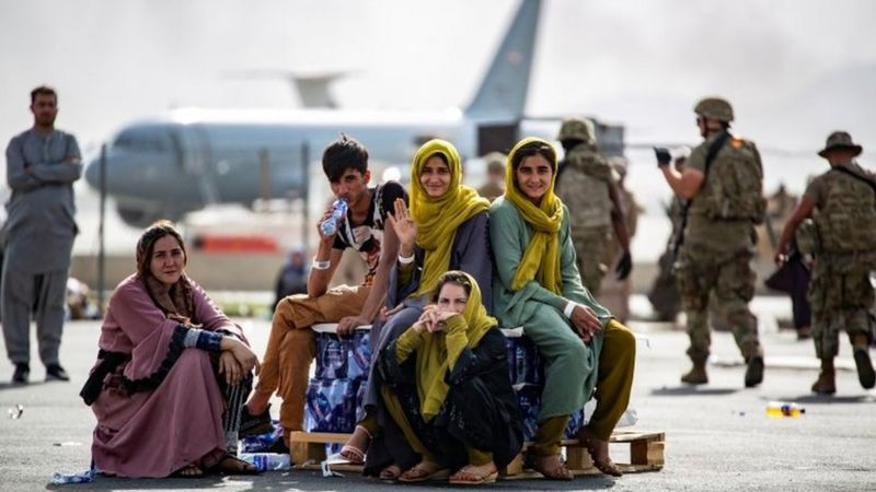 Afghans wave as they wait to board evacuation flights in Kabul