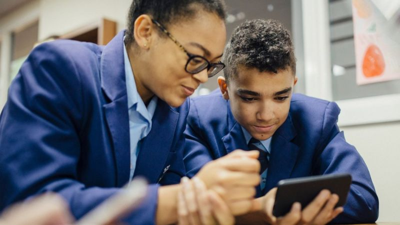 Pupils using a mobile phone in school