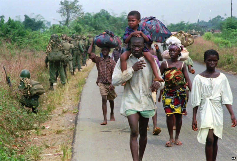 People fleeing the fighting in northwestern Liberia make their way down a road some seven miles from the capital of Liberia, 1995. Soldiers of the West African Peacekeeping Force (ECOMOG), walk in the opposite direction on the side of the road.