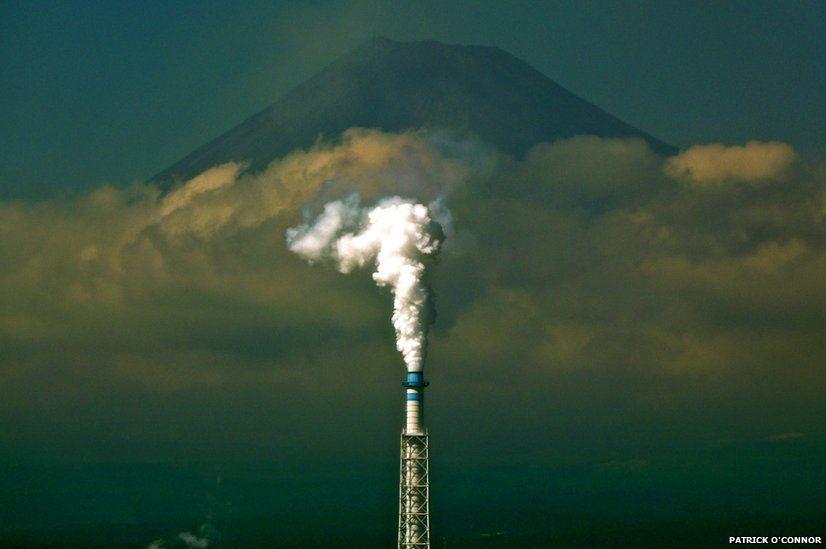 An industrial chimney belching white smoke in front of Mount Fuji, Japan