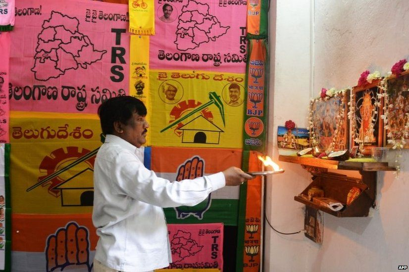 An Indian man offers prayers as he stands in front of different party campaign flags displayed at his workshop in Hyderabad.