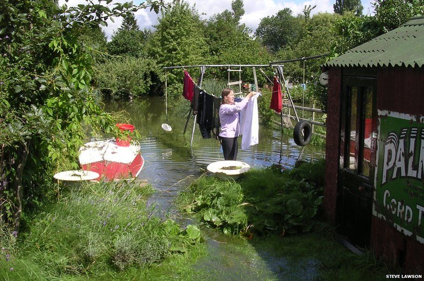 Woman hanging washing in flooded garden