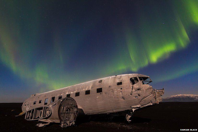 Aurora lights over a Dakota aircraft in Iceland