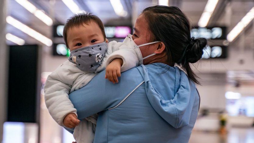 Una madre y un niño pequeño usando mascarillas en China.