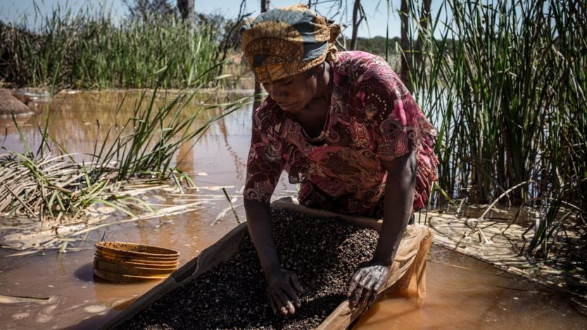 A woman separates cobalt from mud and rocks near a mine between Lubumbashi and Kolwezi in the DRC.
