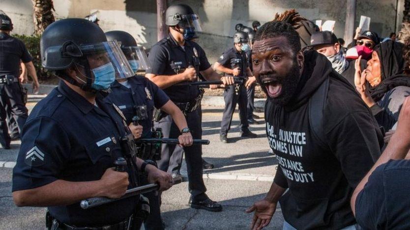 Un manifestante confronta a policías