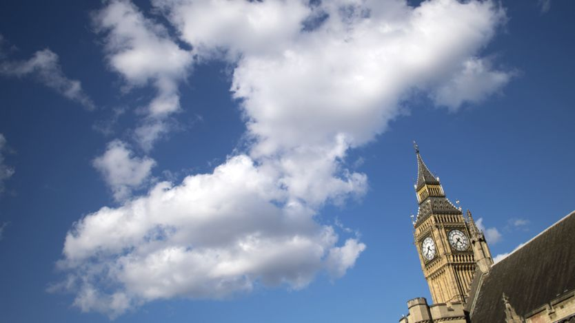The very top of Big Ben seen against a backdrop of a blue sky with white clouds