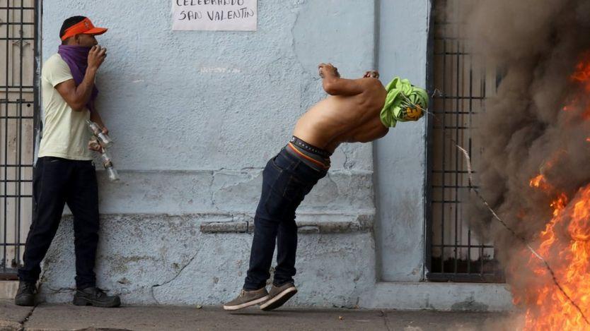 یک معترض از سیم خارداری که خیابانی در شهر یورنا را مسدود کرده عبور میکند