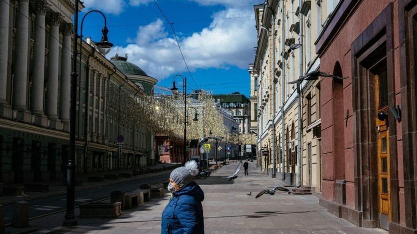 A woman walks down a deserted street in central Moscow on April 21, 2020