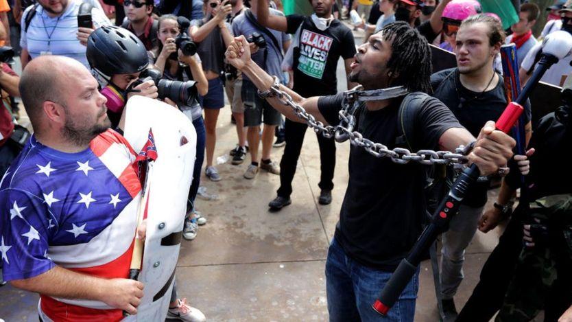 Un manifestante negro con cadenas se enfrenta a otro blanco con una camiseta de la bandera estadounidense