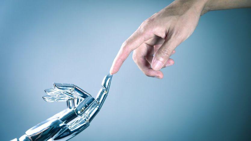Mano robot tocando con un dedo otro dedo de una mano humana.