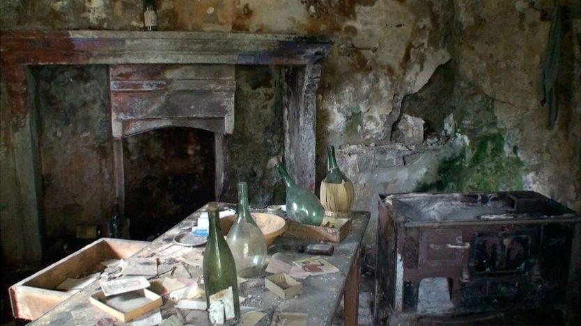 Interior de casa abandonada em Corippo, com ladeira e garrafas vazias em uma mesa