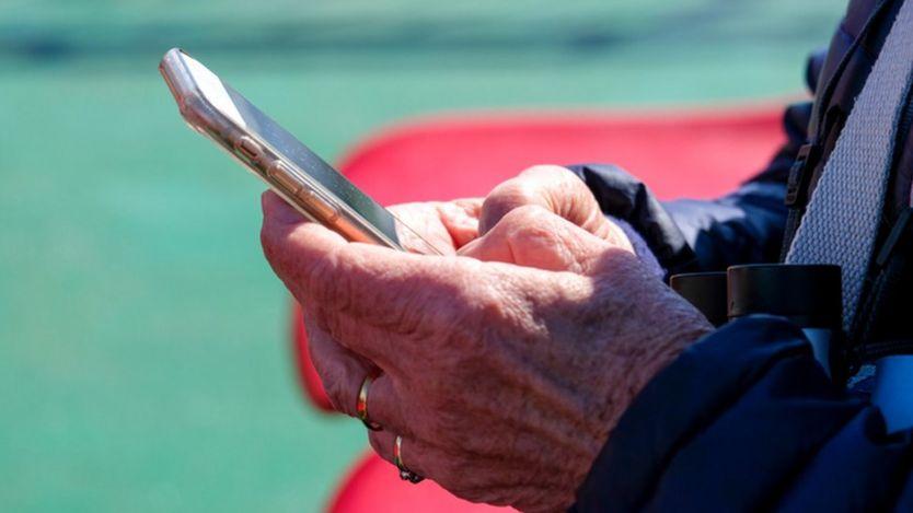 Una persona adulta escribe en un teléfono.
