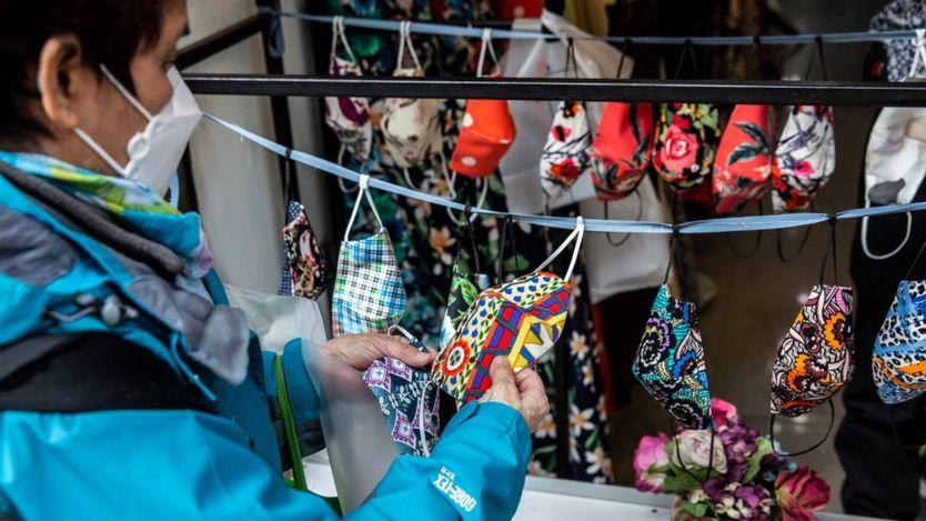 Un comprador en Hong Kong mira mascarillas de distintos colores en un mercado.