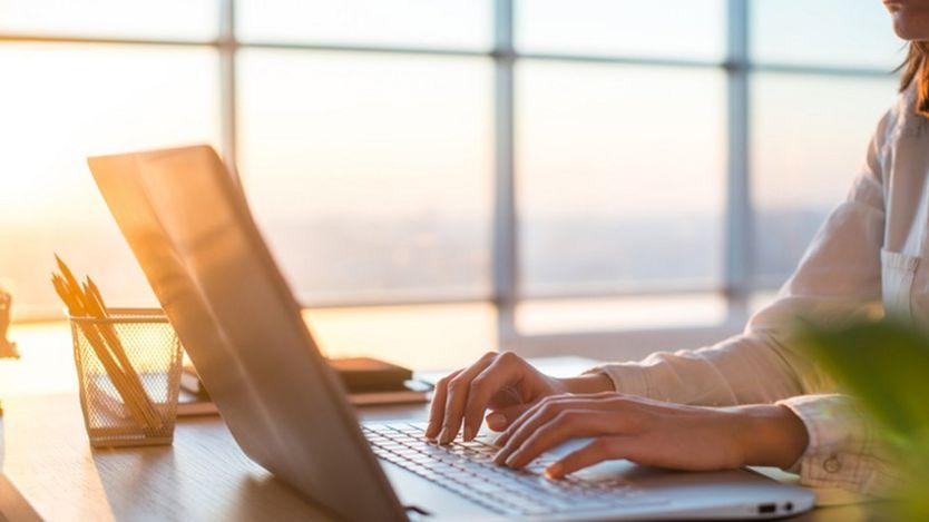 Una mujer escribe en computadora.