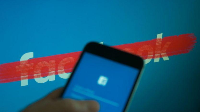 Celular con la aplicación de Facebook, delante de un logo de Facebook tachado.