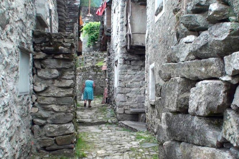 Senhora de vestido azul caminha de bengala por via estreita de Corippo, ladeada por paredes de pedras