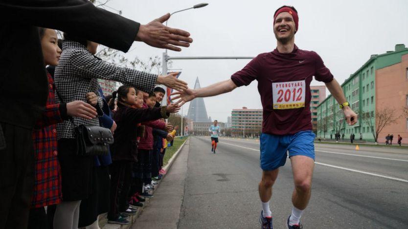 A foreign runner high-fives North Koreans as he runs the marathon