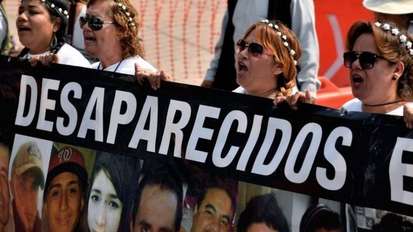 Mothers hold portraits of their missing sons during a march against the government in demand of the clarification of the disappeared in Mexico City on May 10, 2017