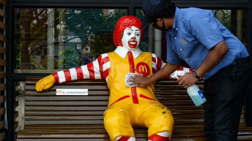 A worker cleans the mascot of fast-food company McDonald's for the reopening of the outlet in Hyderabad on May 20.