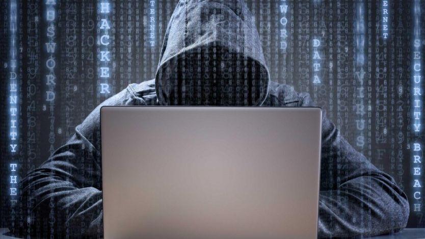 Un hacker trabajando en una laptop, con un sweater con capucha