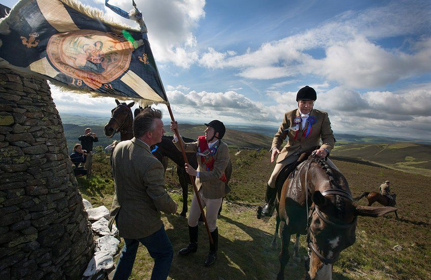 Royal Burgh Standard Bearer Martin Rodgerson and his Burleymen attendants, arrive at the Three Brethren cairns summit