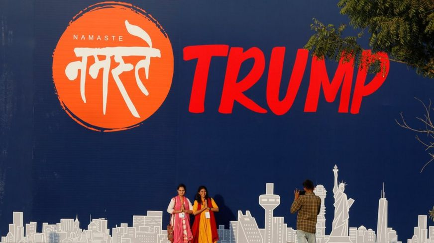 "People pose for a picture in front of a hoarding of the ""Namaste Trump"""