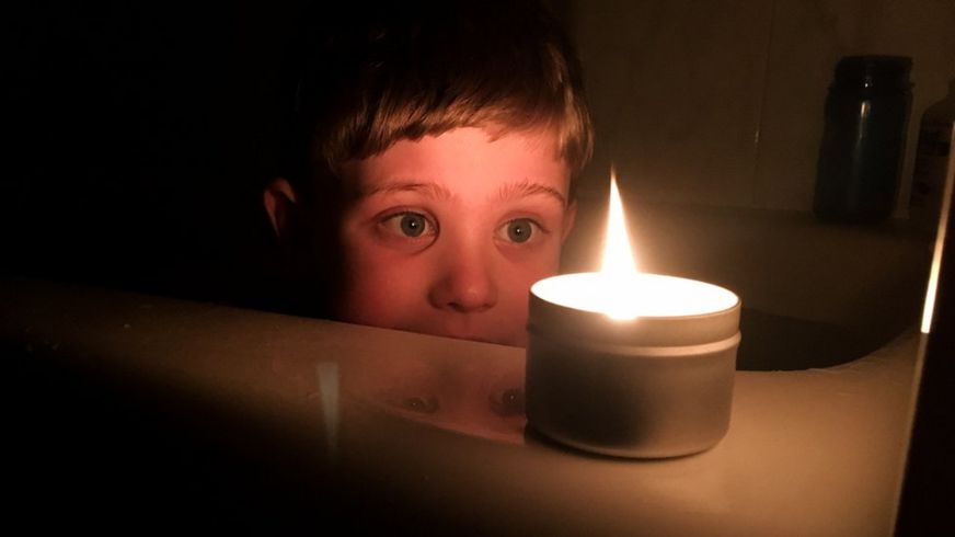 Child looks at candle in a dark room (file photo)