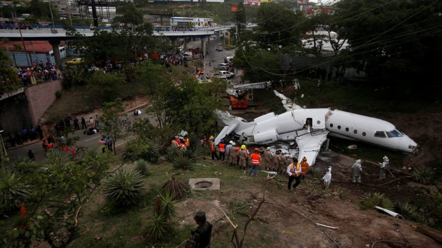 A general view shows rescue workers next to the wreckage of a Gulfstream G200 aircraft