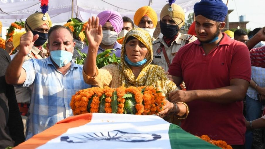 Kashmir Kaur (C) gestures after laying the wreaths of flowers on the coffin of her son and soldier Satnam Singh