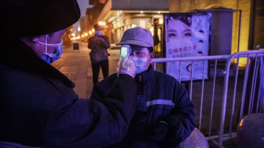 A Chinese worker wears a protective mask as she has her temperature checked on a nearly empty commercial area on February 12, 2020 in Beijing, China.