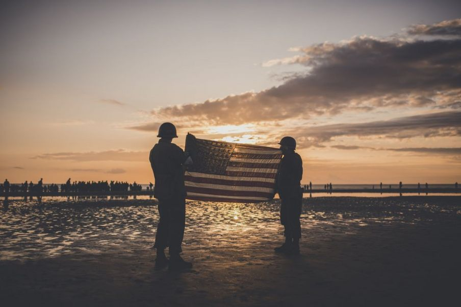 People dressed as US soldiers hold the US flag on Omaha beach
