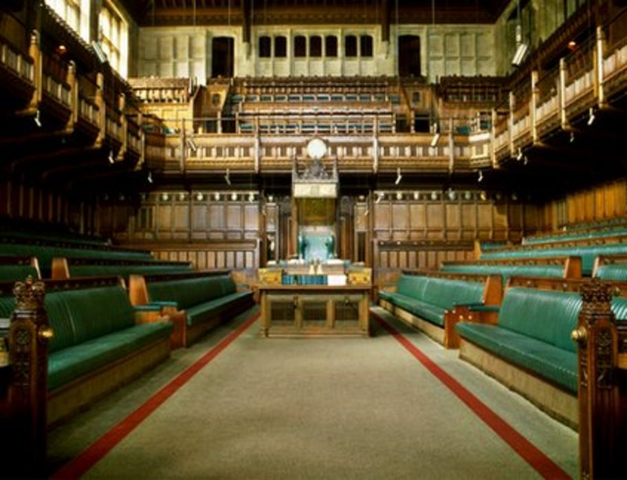 An Empty House Of Commons. It Is A Wooden Interior With Many Rows Of Green