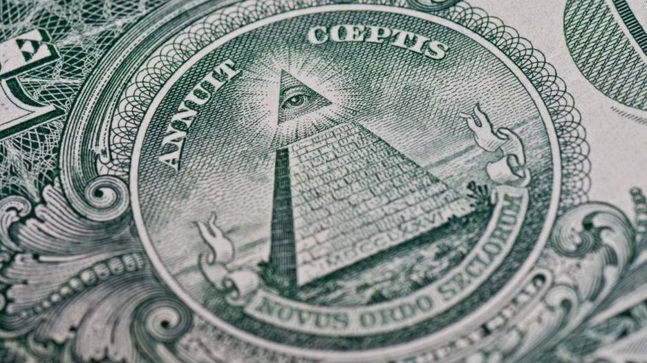 คนที่เชื่อในทฤษฎีสมคบคิดมองว่า สัญลักษณ์บนธนบัตรเงินดอลลาร์สหรัฐฯ สื่อถึงอิทธิพลของอิลลูมินาติ